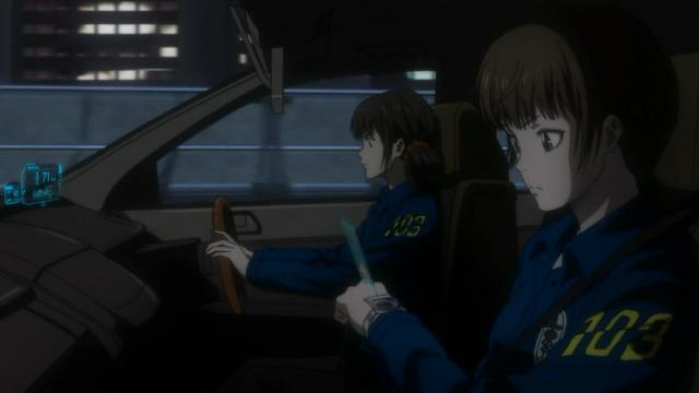 As inspetoras. Tsunemori em primeiro plano, e a novata dirigindo o carro